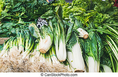 Various fresh green vegetables and herbs on market stall