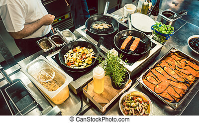 Various fresh ingredients on the stove of a commercial kitchen