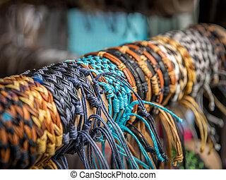 Various friendship bracelets on a wooden pole for sale