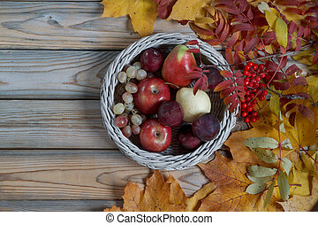 Various fruits are lying in a wicker basket. Autumn still life. Copy space for your text.