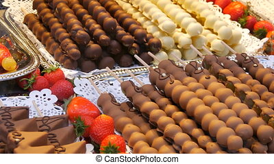 Various fruits on a wooden skewer stick in a caramelized glaze made of milk black white chocolate. Grapes, banana, strawberries in icing on the counter of the Christmas market