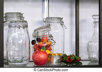 Various glass new empty jars with clip for canning vegetables, fruits and berries on the shelf