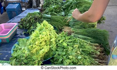 Various greenery on counter in market - Crop woman selecting...