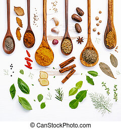 Various herbs and spices in wooden spoons. Flat lay of spices ingredients chilli ,pepper, garlic, dries thyme, cinnamon, star anise, nutmeg, rosemary, sweet basil and kaffir lime on wooden background.