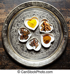 Various herbs in white heart shaped dishes