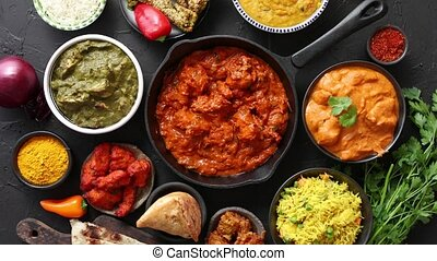 Various Indian dishes on a table. Spicy chicken Tikka Masala...