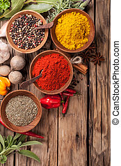 Various kind of spices on wooden table, shot from aerial ...