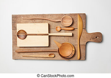 Various kitchen utensil on white wooden background. Cutting board, fork, knife and spoon
