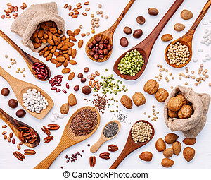 Various legumes and different kinds of nuts in spoons. Walnuts kernels ,hazelnuts, almond ,brown pinto ,soy beans ,flax seeds ,chia ,red kidney beans and pecan set up on white wooden table.