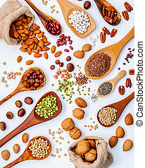 Various legumes and different kinds of nuts in spoons