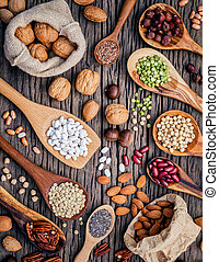 Various legumes and different kinds of nutshells in spoons. ...