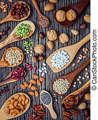 Various legumes and different kinds of nutshells in spoons