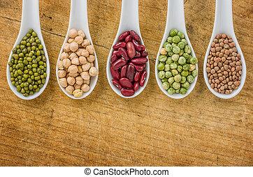 Various legumes on porcelain spoons
