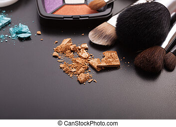 Various makeup products on dark black background with copyspace