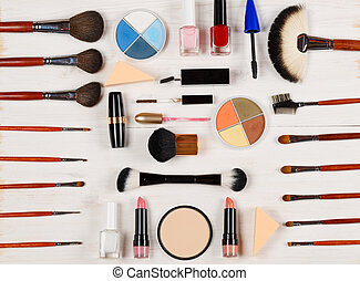 Various makeup products on wooden background