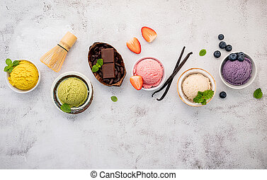 Various of ice cream  flavours in bowl blueberry ,green tea ,coconut ,strawberry and chocolate  setup on white stone background .