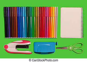 various office supplies on a green surface