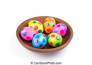 Various painted chicken easter eggs in wooden bowl on white