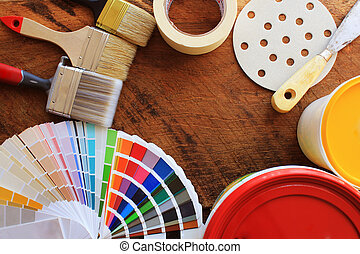 various painting tools, accessories and color samples for home renovation on wooden background