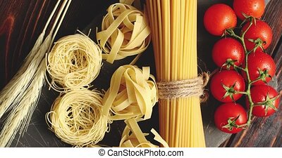 Various pasta and tomatoes with garlic - Top view of...
