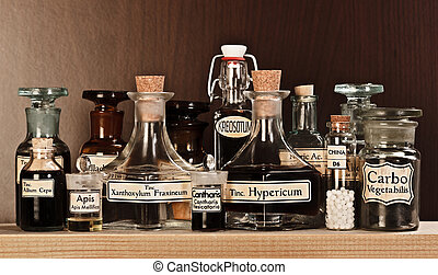 Various pharmacy bottles of homeopathic medicine on dark...