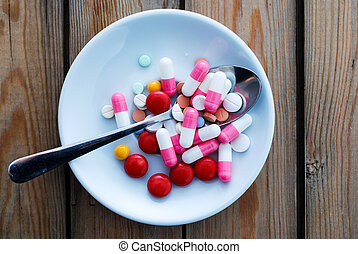 various pills in a white plate on wood background,