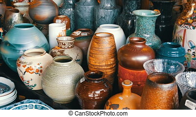 Various porcelain and clay jugs on the counter of store -...