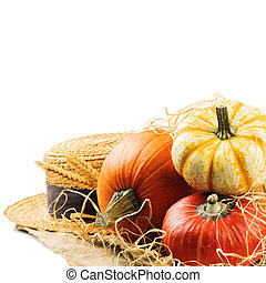 Various pumpkins and straw hat