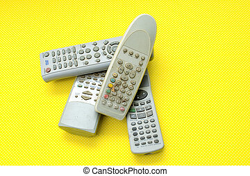 Various remote controls on yellow background