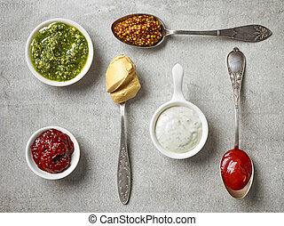 various sauces in bowls and spoons