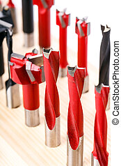 various shapes drill bits for wood on wooden stand. close-up