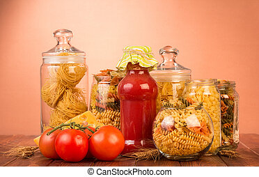 Various shapes pasta in jars, bottle ketchup, tomato on brown.
