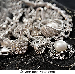 Various silver shining jewellery and closeup pearl on black