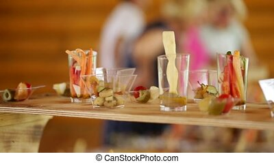 Various snacks on a buffet table at the event, the camera moves smoothly.