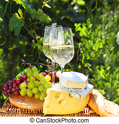 Various sorts of cheese, bread, grapes and two glasses of the white wine. In the vineyard