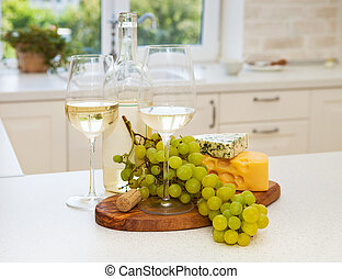 Various sorts of cheese, grapes and two glasses of the white win