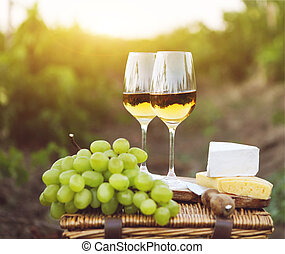 Various sorts of cheese, grapes and two glasses of white wine