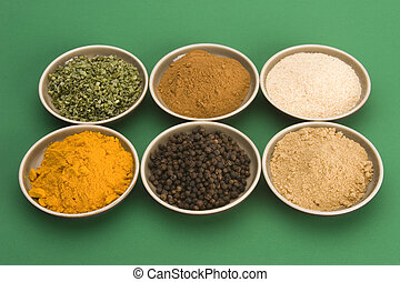 Various spice bowls agains a plain background