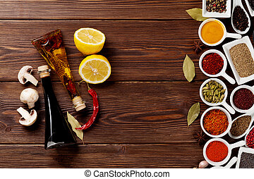 Various spices and condiments on wooden background with copy...