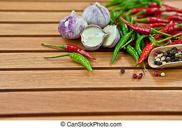 Various spices, garlic and peppers on a wooden background