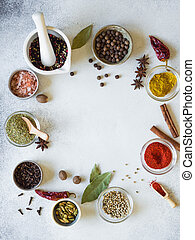 Various spices in bowls and pestle frame on the table. dry herbs, salt spices on a gray background.