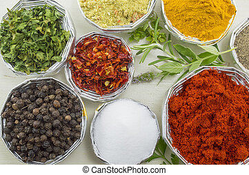 Various spices in shiny bowls on a white wooden table close up