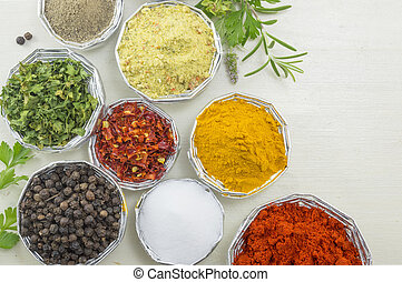 Various spices in shiny bowls on a white wooden table