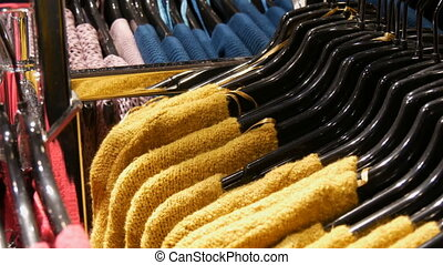 Various stylish knitted multicolored sweaters hanging on...