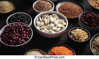 Various superfoods in smal bowls on dark rusty background....