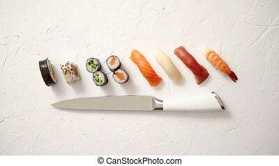 Various sushi rolls with Japanese knife on white stone slate...