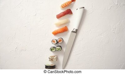 Various sushi rolls with Japanese knife on white stone slate...