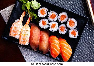 Various sushi served on black plate. Japanese food