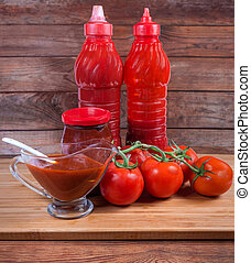 Various tomato sauces in different packings and fresh tomatoes branch