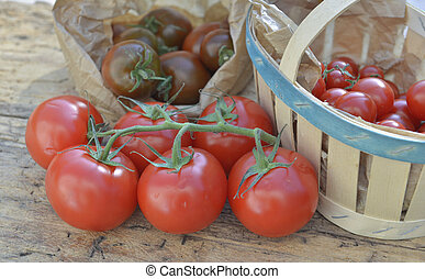 various tomatoes on paper bag or crate on a wooden table